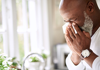 A man with hypertension blows his nose. He's in need of a decongestant that won't raise his blood pressure.