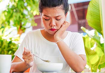 a woman with a low appetite looking at a bowl and holding a spoon